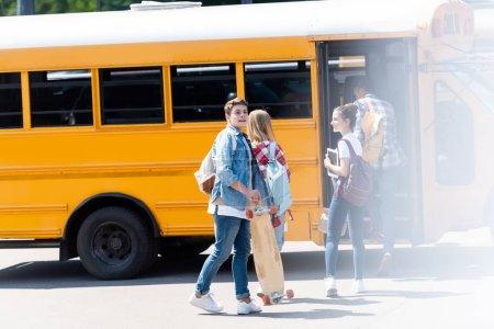Groupe d'érudits teen marchant à l'intérieur de l'autobus scolaire