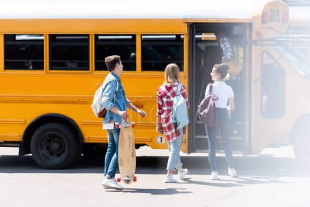 group of teen students walking inside of school bus