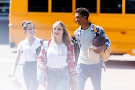 group of happy teen students walking in front of school bus
