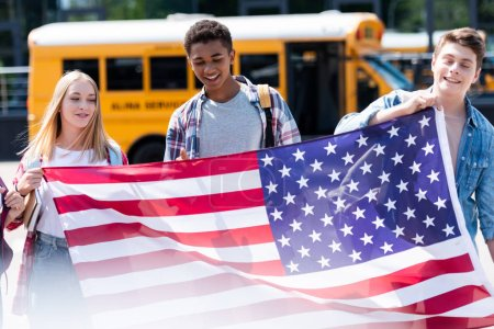 group of smiling teen students holding usa flag in front of school bus
