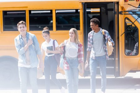 Photo for Group of teen scholars walking together in front of school bus - Royalty Free Image