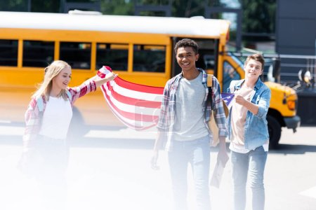 group of happy teen students with usa flag in front of school bus
