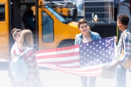 group of american teen scholars with united states flag in front of school bus