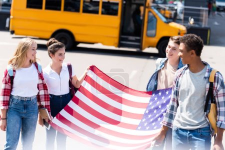 group of multiethnic american teen scholars with usa flag in front of school bus