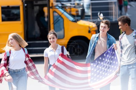 group of american teen scholars walking with usa flag in front of school bus