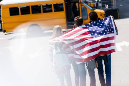 rear view of group of american teen scholars with usa flag in front of school bus