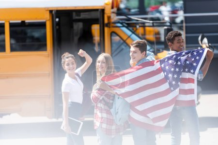 group of happy american teen scholars with usa flag in front of school bus