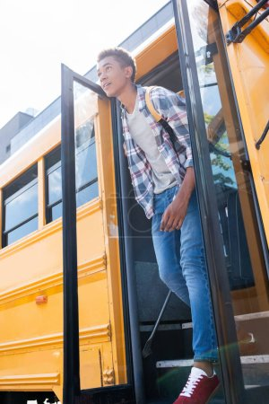 bottom view of happy teen african american schoolboy walking out school bus
