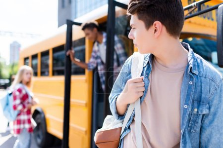 teen schoolboy walking in front of school bus and turning back at classmates