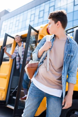 bottom view of teen schoolboy walking in front of school bus and turning back at classmate