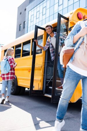 multiethnic teen students walking out of school bus