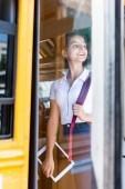 happy teen schoolgirl standing in school bus and looking away