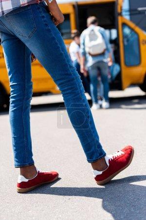 Foto de Recortar el tiro de chico afroamericano de pie delante de autobús escolar - Imagen libre de derechos