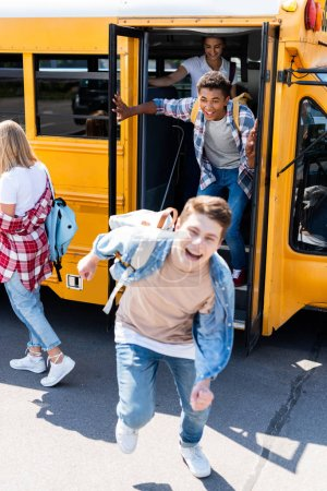 group of joyful teen scholars running at school from bus