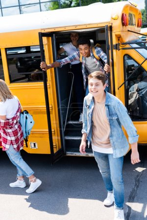 group of teen scholars running at school from bus