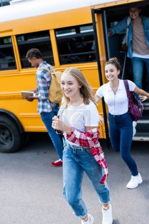 active happy teen scholars running out school bus