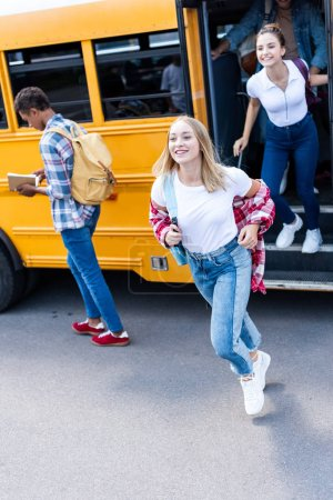 smiling multiethnic teen scholars running out school bus