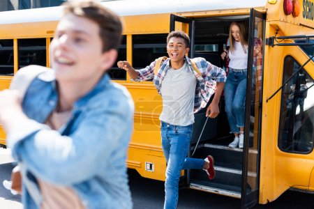 group of teen students running out of school bus