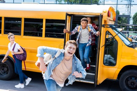 group of teen scholars running out school bus and screaming