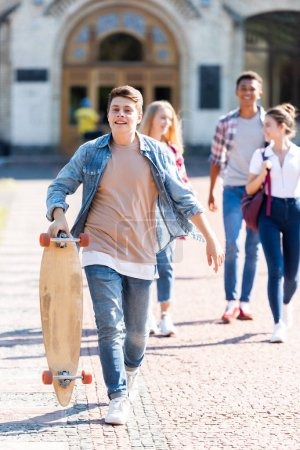 smiling teen schoolboy with skateboard walking with friends after school