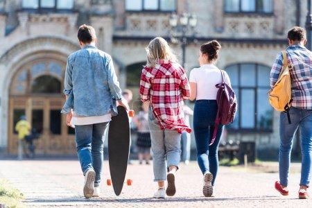 Photo pour Vue arrière du groupe d'adolescents marchant au bâtiment de l'école - image libre de droit