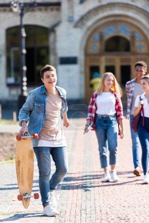 happy teen schoolboy with skateboard walking with friends after school