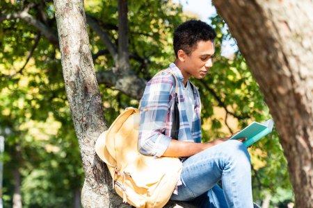 Konzentrierter Teenager liest Buch, während er auf einem Ast sitzt