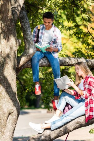 teen students couple relaxing on tree and reading books