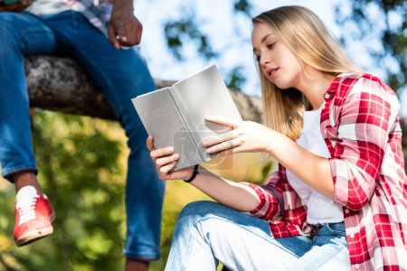 cropped shot of teen students couple reading books while sitting on tree