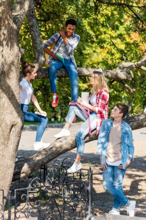 group of happy multiethnic teenagers sitting on tree in park