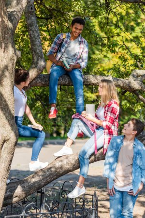 group of happy teenagers sitting on tree in park
