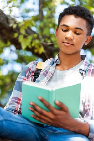 bottom view of focused teen student reading book under tree