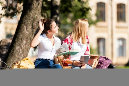 teen schoolgirls sitting on bench and reading homework together