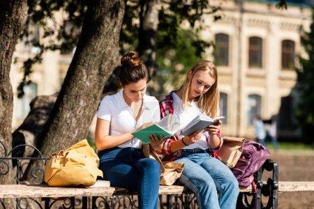 teen schoolgirls sitting on bench and doing homework together