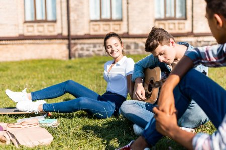 group of happy teenagers sitting on grass and playing acoustic guitar during lunch