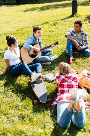 group of teenagers spending time together and listening to guitar song