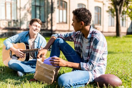 happy teenagers sitting on grass and playing acoustic guitar during lunch