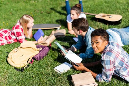 group of multiethnic teen scholars lying on grass and studying together