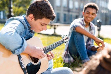 Foto de Adolescentes felices sentados en el césped y tocar la guitarra acústica - Imagen libre de derechos