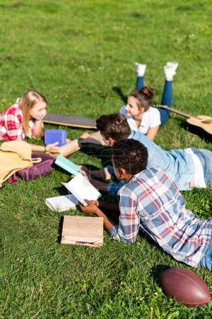 group of teen scholars lying on grass and studying together