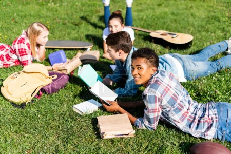 group of happy teen scholars lying on grass and studying together