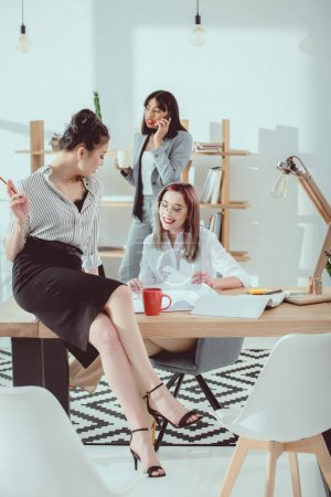 Multiethnic group of attractive young businesswomen in formal wear working together in modern office