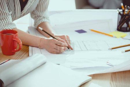 Photo pour Photo recadrée de femme d'affaires à l'aide de crayon pendant le travail avec les bleus - image libre de droit