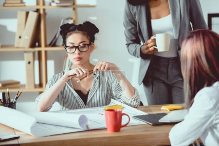 Photo for Serious asian businesswoman in eyeglasses sitting at table with colleagues and working in office - Royalty Free Image