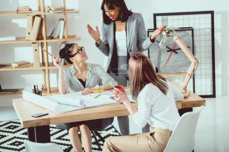 Foto de Sonrientes a jóvenes empresarias trabajando con planos en oficina moderna - Imagen libre de derechos