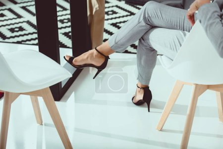 Cropped shot of businesswoman in suit and high heeled shoes sitting in chair in office