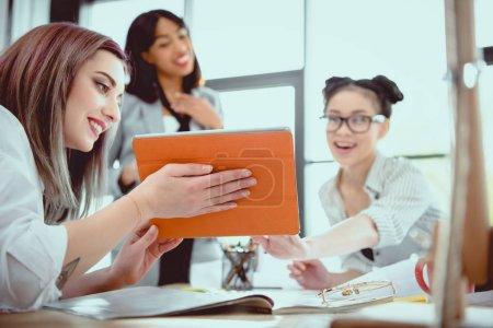 Photo pour Jeunes femmes travaillant ensemble et en utilisant la tablette numérique au bureau - image libre de droit