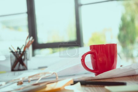 Close-up view of various office supplies, coffee cup and blueprints on office table