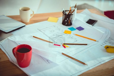 Close-up view of blueprints with office supplies and cups of coffee on table