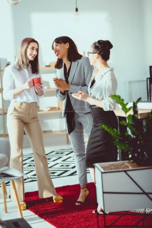 young multiethnic businesswomen drinking coffee and talking at office